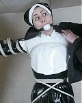 Religi�ses Latexgirl wird mit einem Mundknebel und strammen Bondageseilen versehen und an das Kreuz gebunden